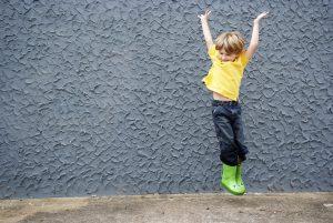 Skaczący chłopiec z rękami wzniesionymi ku górze