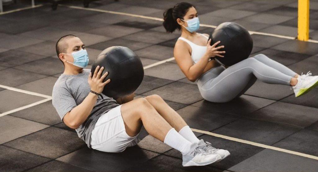 Chłopak z dziewczyną ćwiczą z piłką rehabilitacyjną